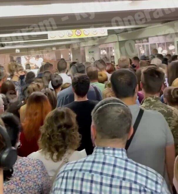 Люди стоят в очереди, чтобы попасть в вестибюль станции.