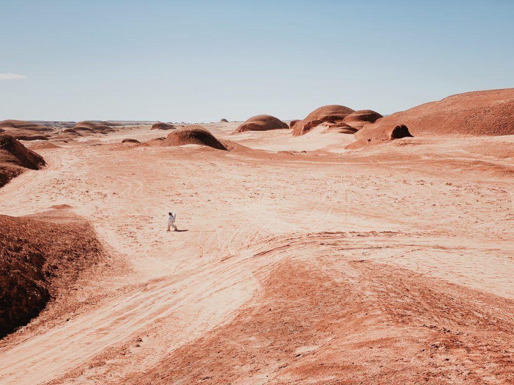 Фото астронавта, гуляющего по марсианским полям