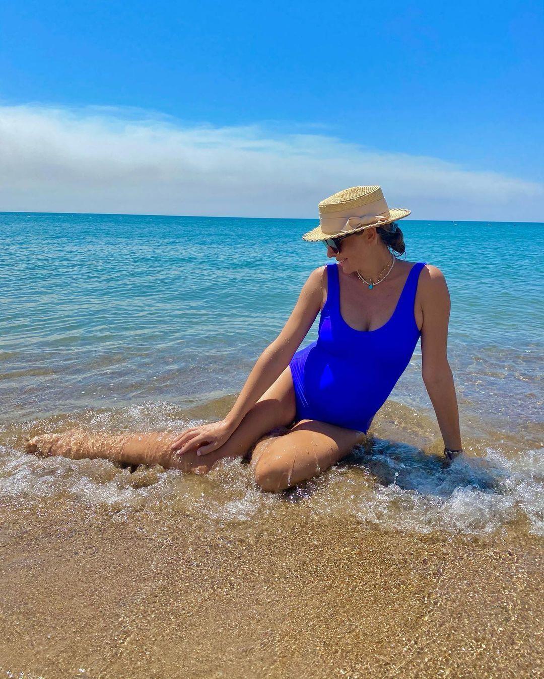 Осадча позувала сидячи на піску з краєвидом на море