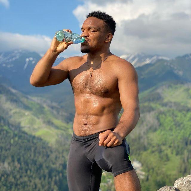 Жан Беленюк позирует на фоне гор.