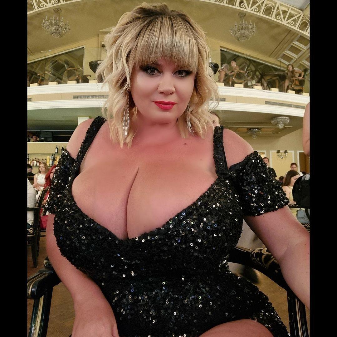 Мила Кузнецова в облегающем платье с глубоким вырезом.
