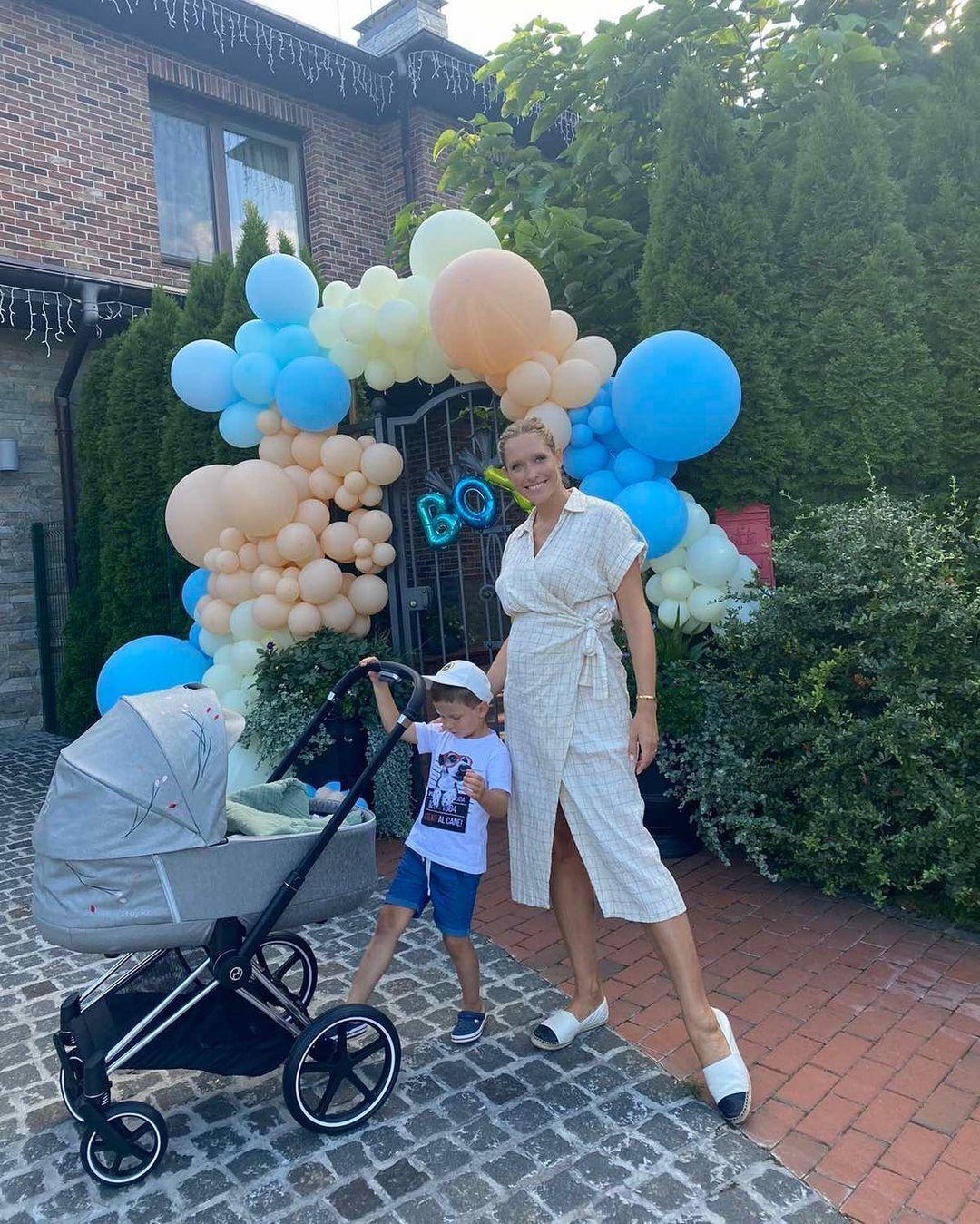 Катя Осадчая возле своего дома с 4-летним сыном и новорожденным малышом