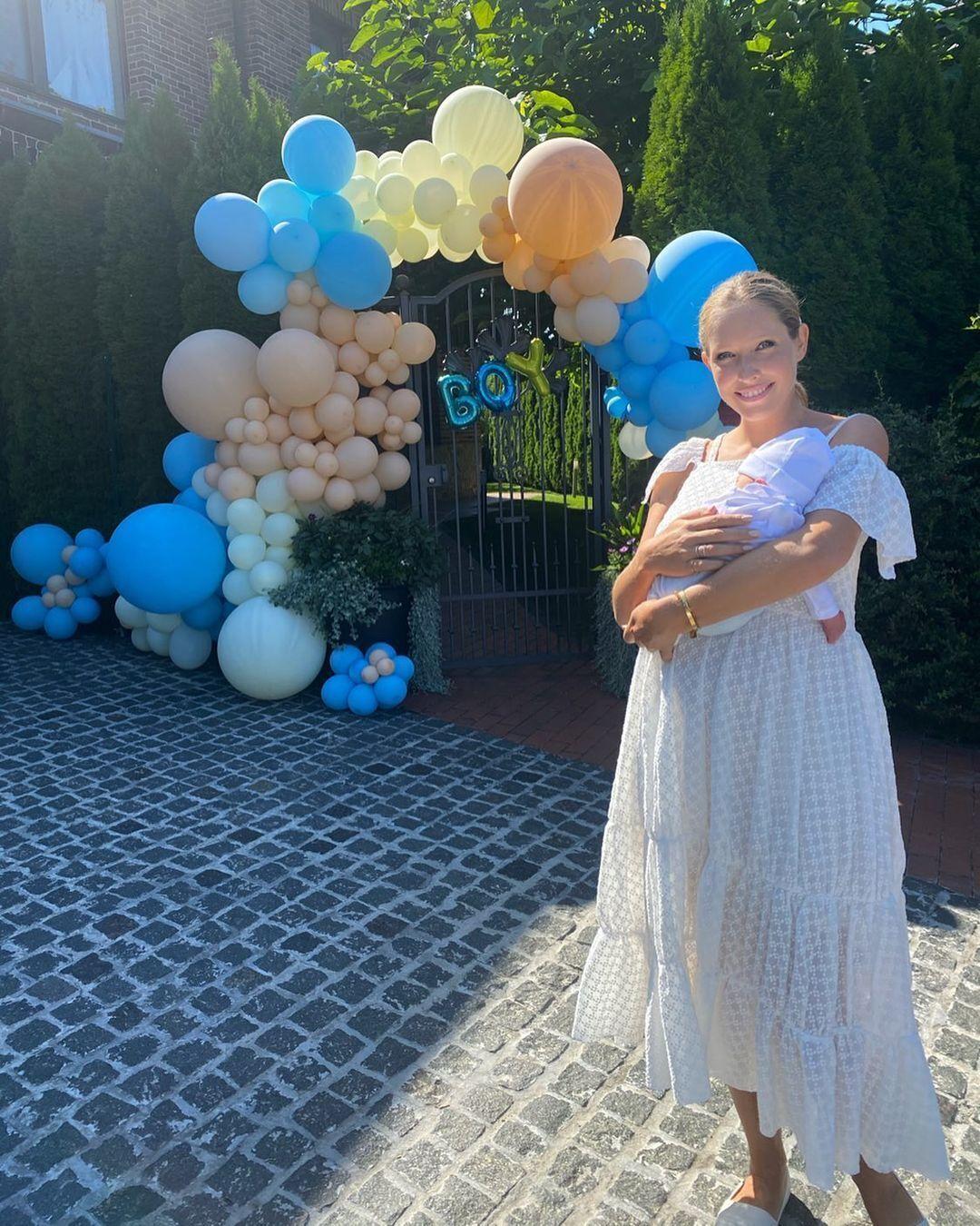 Катя Осадчая возле своего дома с новорожденным сыном