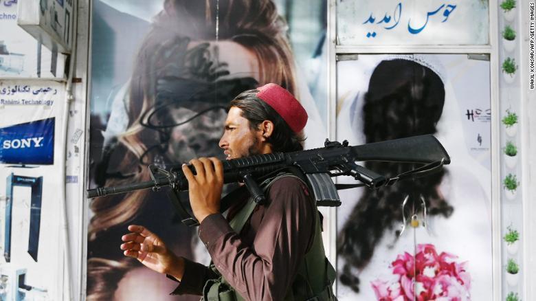 """Солдат """"Талибана"""" возле плакатов, на которых краской зарисованы фотографии женщин"""