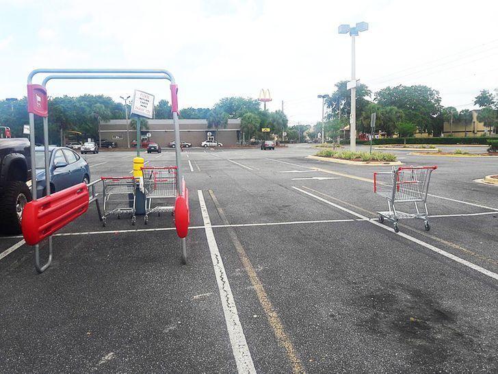 Люди залишають візки на парковці.