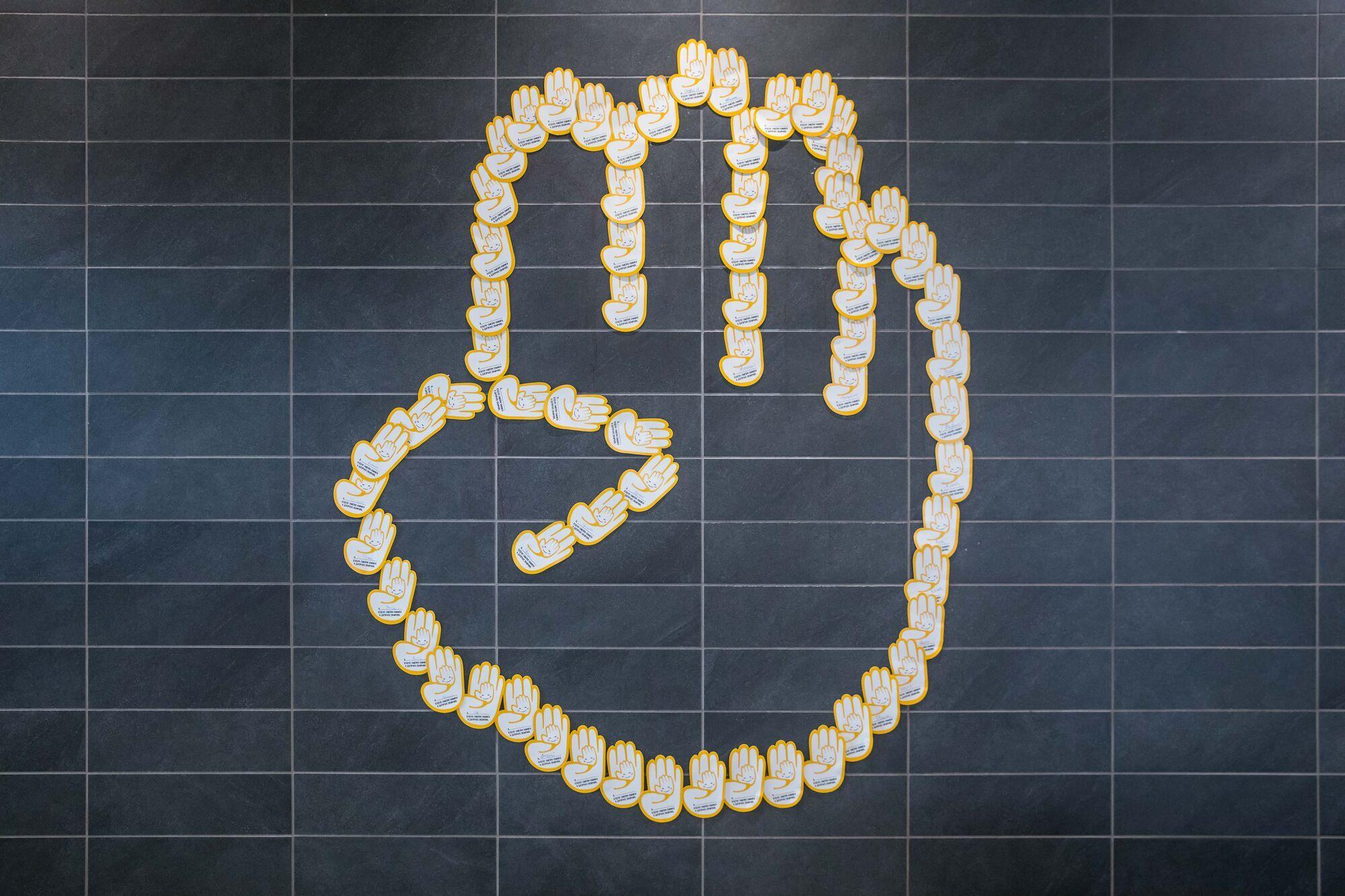 Желто-белая бумажная ладошка празднует юбилей – 20 лет