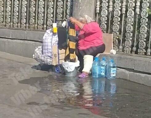 Жінка зливала воду під ноги пішоходам.