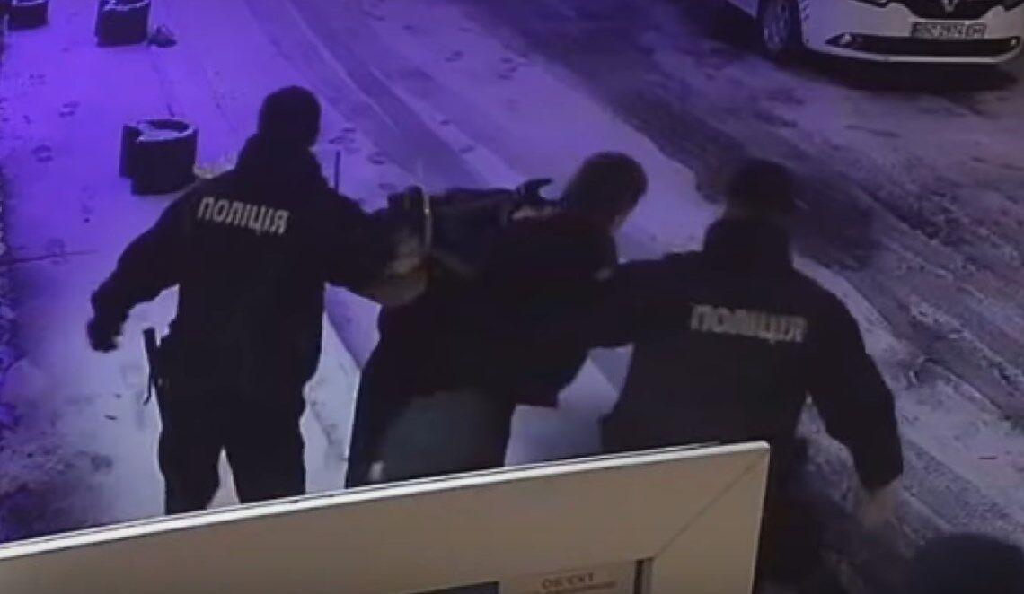 Поліцейські виводять хлопця із салону з гральними автоматами.