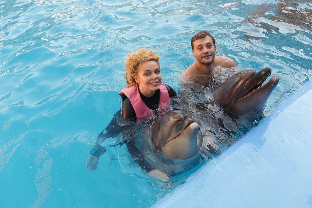 Аліна і Роман плавають з дельфінами.