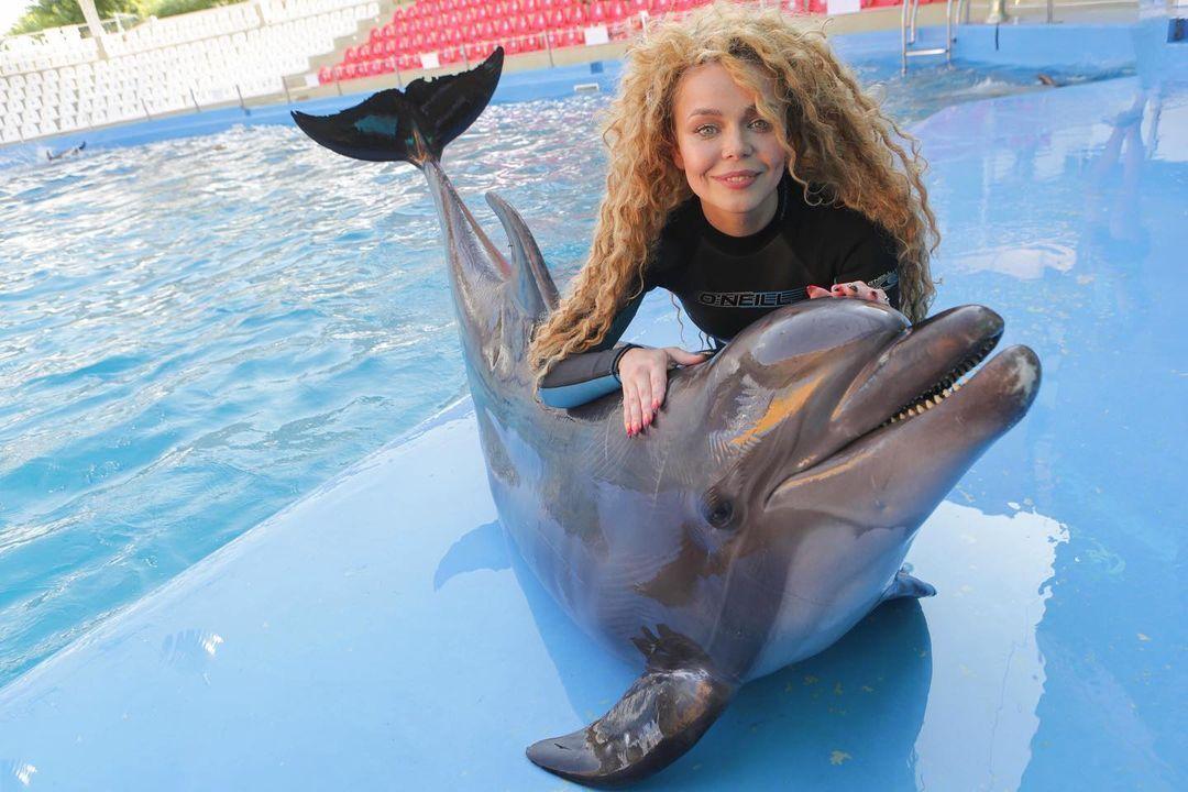 Аліна Гросу фотографується з дельфіном.