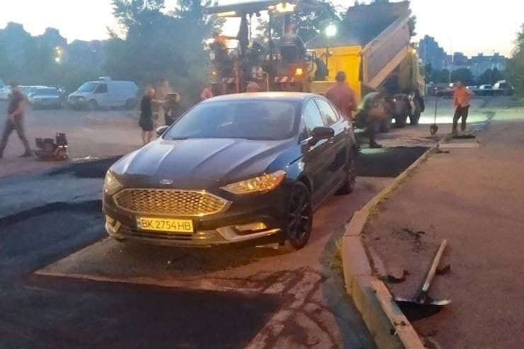 В Киеве дорожники положили асфальт вокруг авто, которое стояло на обочине 4 дня.