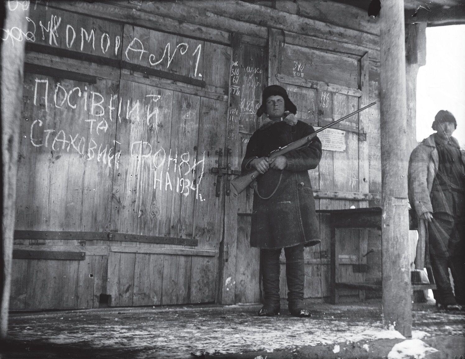 Вооруженный комсомолец охраняет кладовую с хлебом, село Ольшаны, Харьковская область