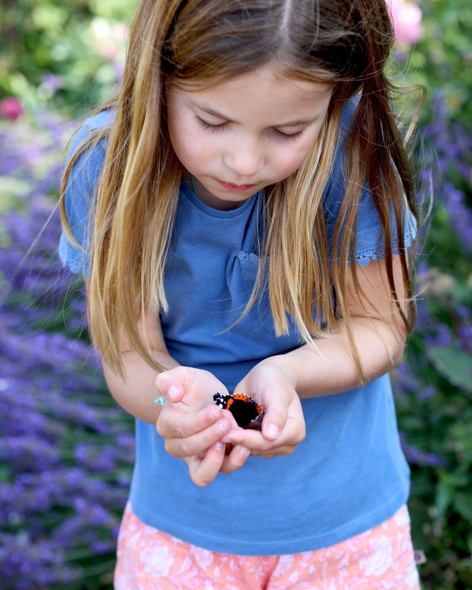 Принцесса Шарлотта нежно держит в руках бабочку вида красный адмирал