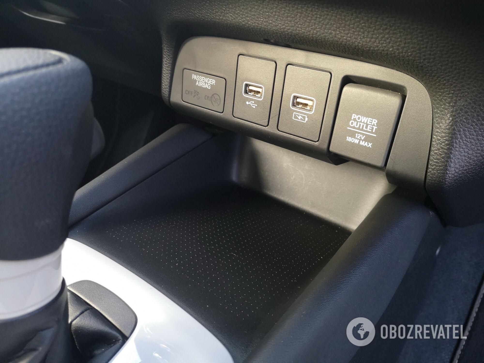 В нижней части консоли есть USB-порты, розетка на 12 В, а также индикатор состояния подушки безопасности
