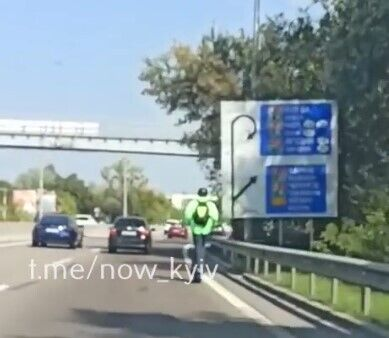 Мужчина на самокате ехал по оживленной дороге.