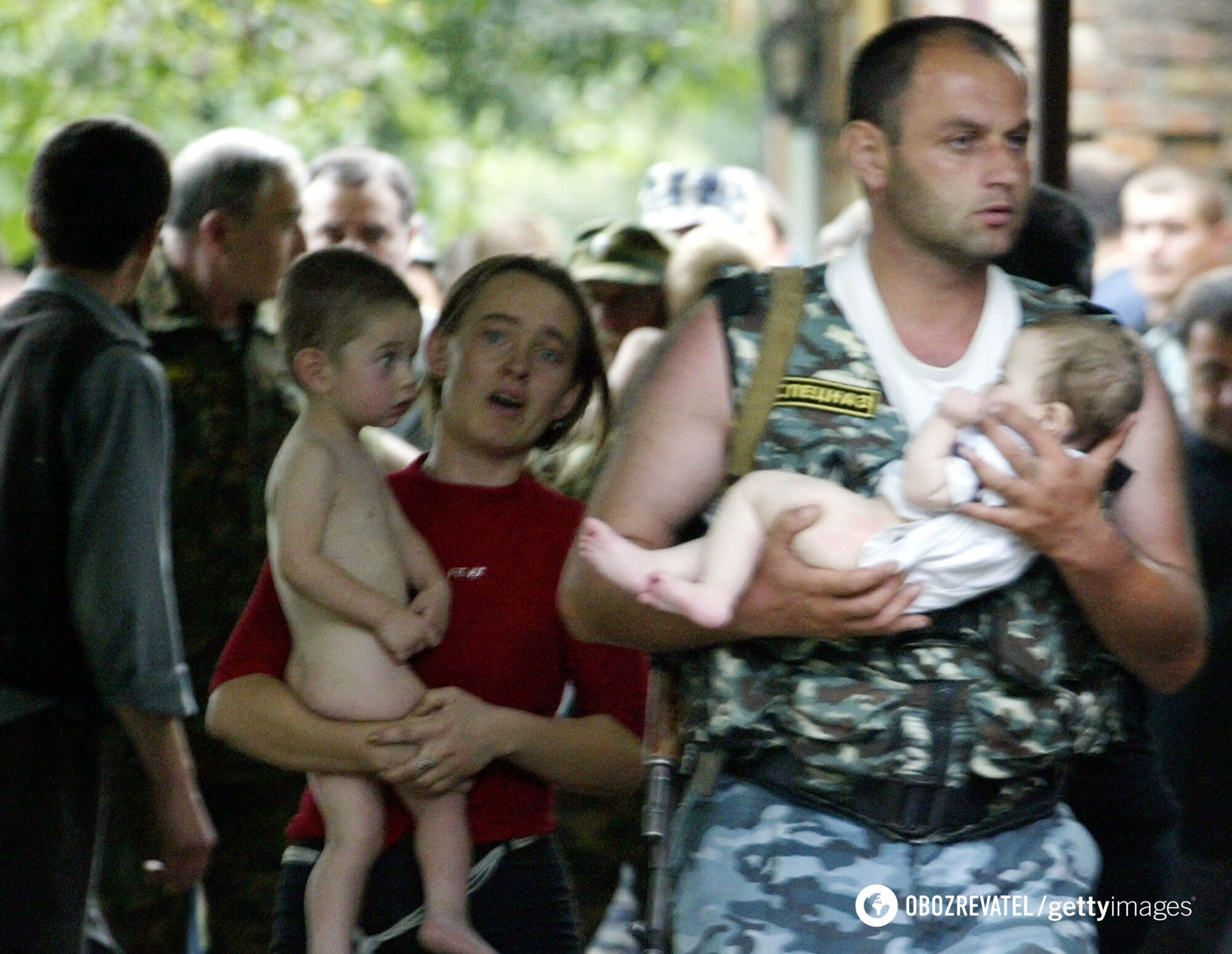 Сотрудник полиции и женщина несут двух освобожденных детей из захваченной школы в Беслане
