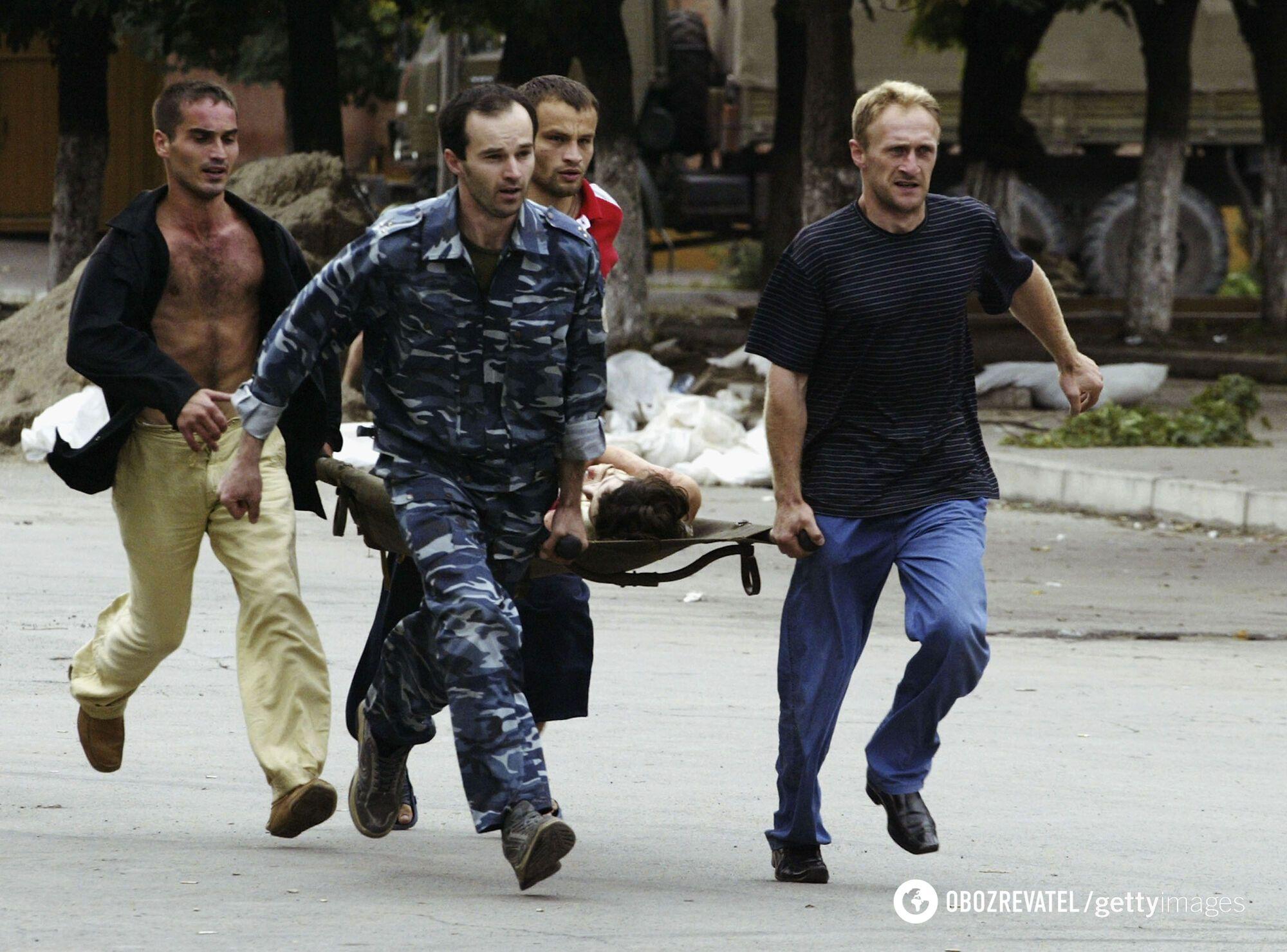 Добровольцы несут раненую из захваченной школы, 3 сентября 2004 года, Беслан