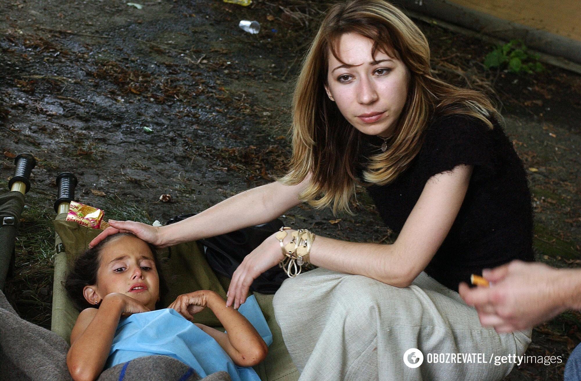 Осетинка утешает девочку во время спасательной операции в школе Беслана, 3 сентября 2004 года