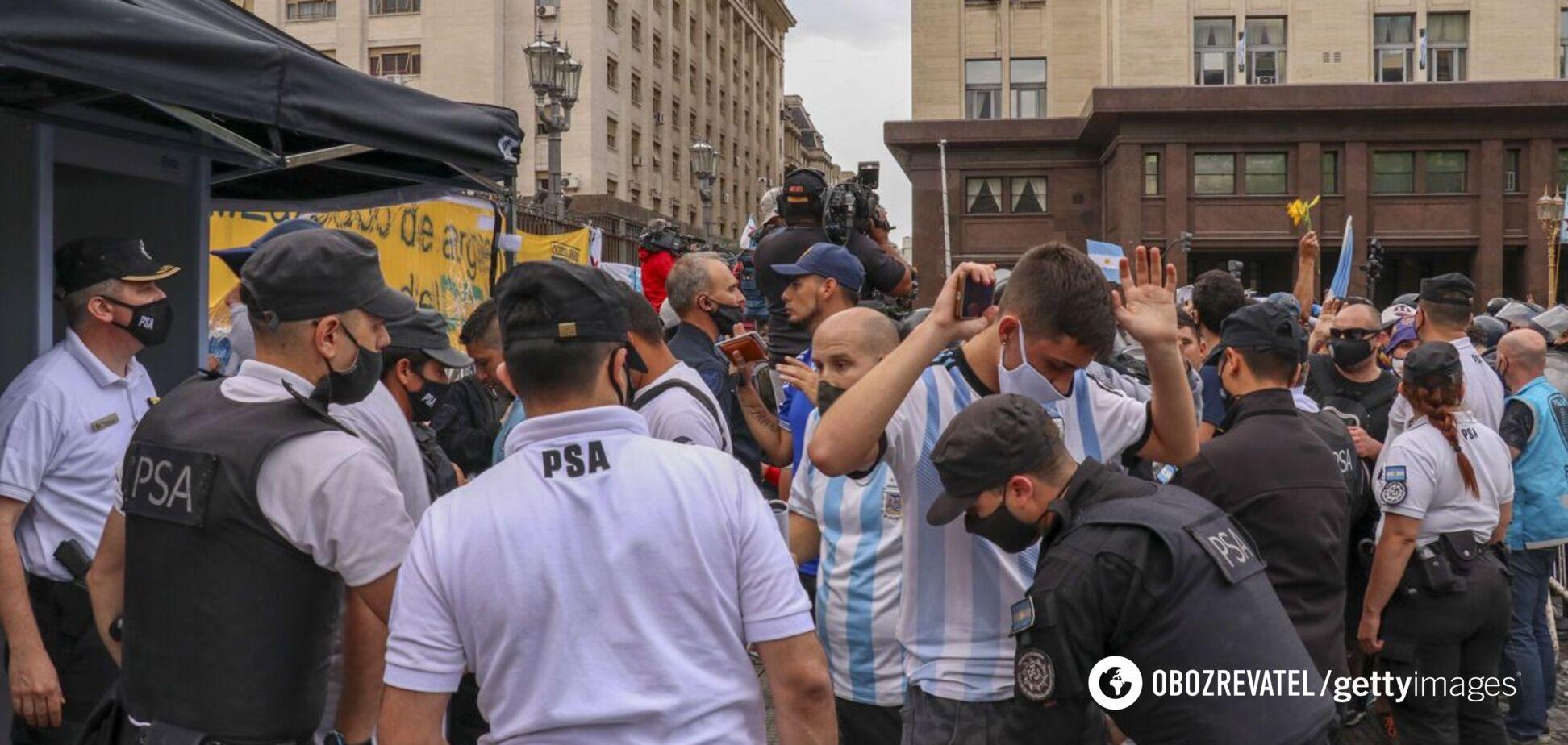 Одного из поклонников Марадоны обыскивают перед входом в президентский дворец
