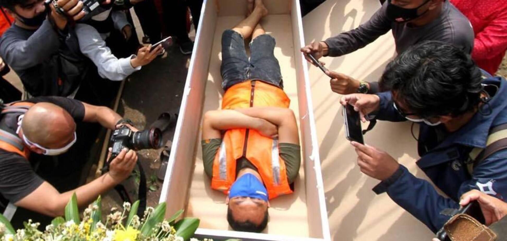 В Джакарте полиция людей без маски просит полежать в гробу