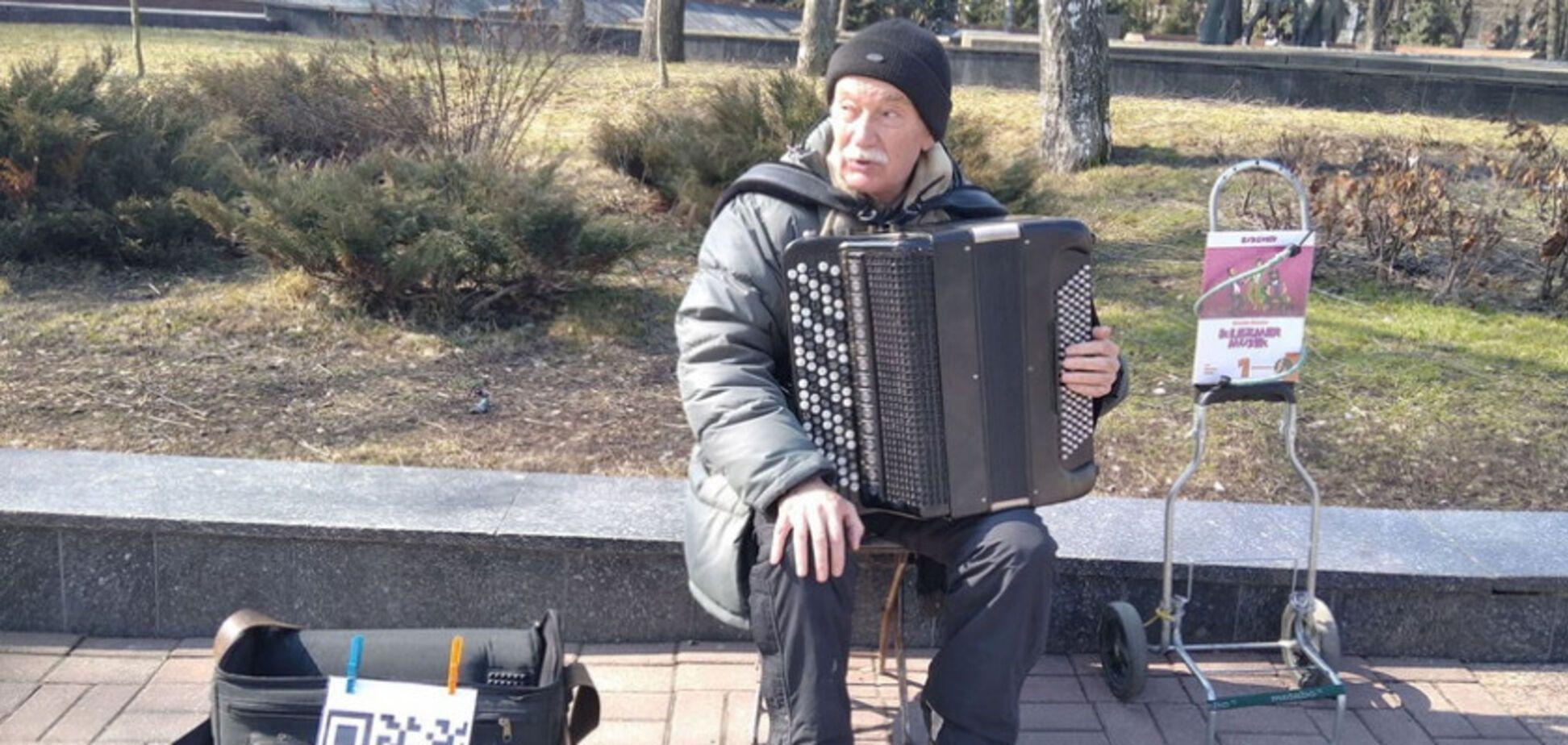 Вуличний музикант Олександр Шамігов приймає гроші через QR-код