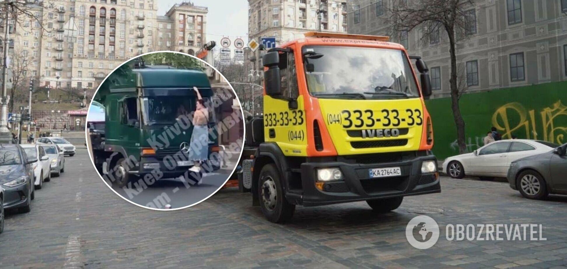 В Киеве женщина залезла на кабину эвакуатора, 'спасая' свое авто. Видео